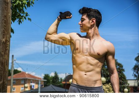 Shirtless fit athletic young man doing bicep pose outdoor