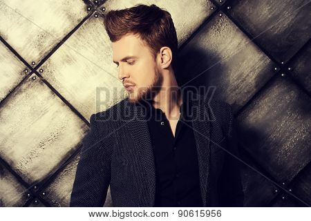 Vogue shot of a handsome man in black suit posing at studio. Men's beauty, fashion.