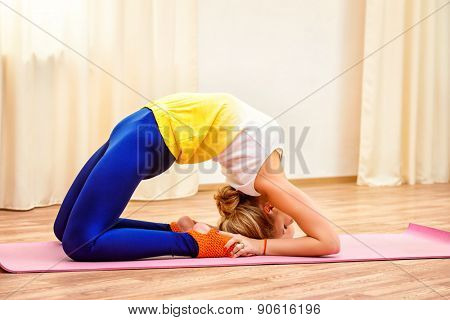 Slender athletic girl doing yoga exercises indoor. Backbend.