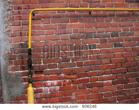 Red Brick Wall With Yellow Gas Tube