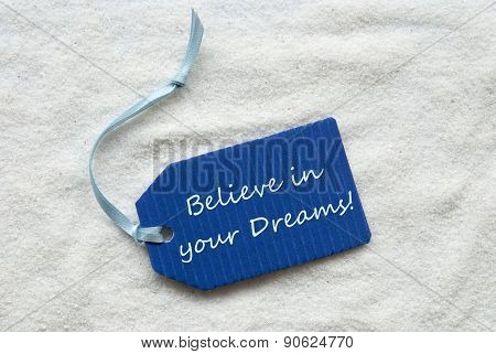 One Blue Label Or Tag With Light Blue Ribbon On White Sand Background With English Quote Believe In Your Dreams poster