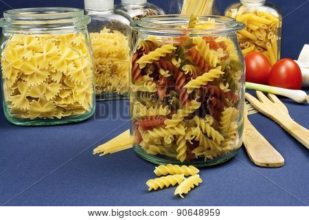 different kinds of pasta on the table, together with vegetables, ready for cooking