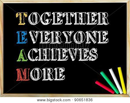 Acronym TEAM as Together Everyone Achieves More. Written note on wooden frame blackboard colored chalk in the corner. Motivational Concept image poster