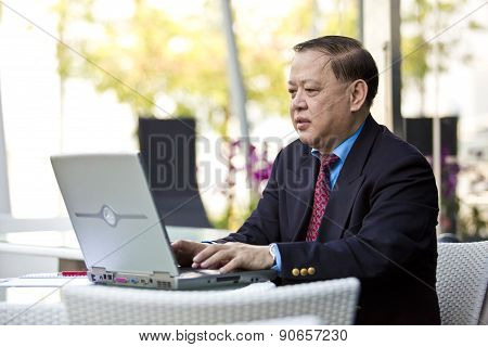 Senior Asian businessman using laptop PC