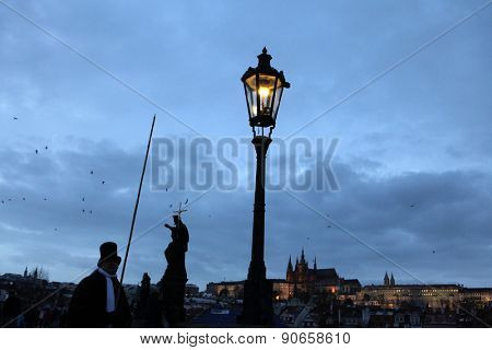 PRAGUE, CZECH REPUBLIC - DECEMBER 10, 2012: Lamplighter lights a street gas light manually during the Advent at the Charles Bridge in Prague, Czech Republic.