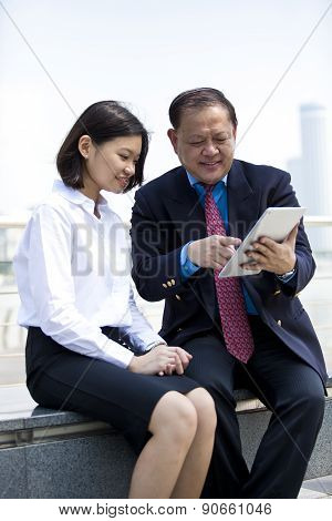 Senior Asian businessman and young female executing using tablet PC