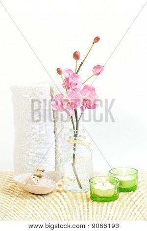 Composition of Pink orchid, towel and two candles
