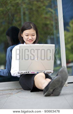 Young Asian female executive using laptop PC