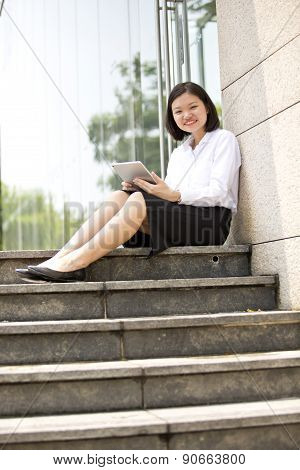 Young Asian female executive using tablet PC