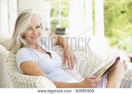 Senior Woman Sitting Outside Reading Magazine