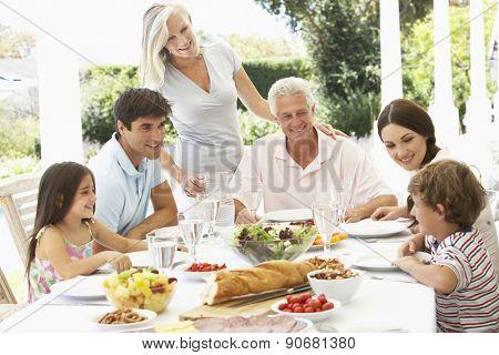 Three Generation Family Enjoying Meal Outdoors