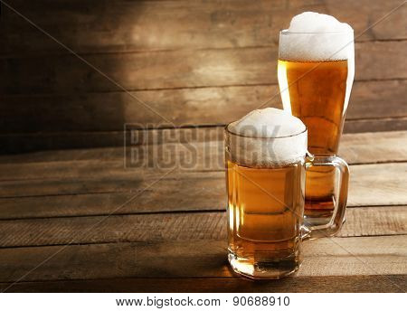 Glasses of beer on wooden background