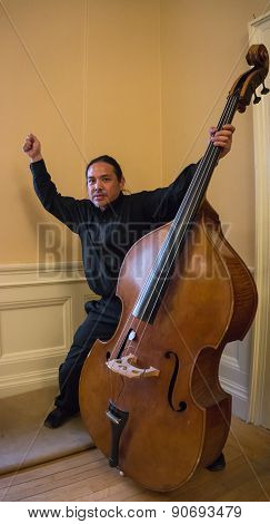 exuberant Asian musician  with his Bass