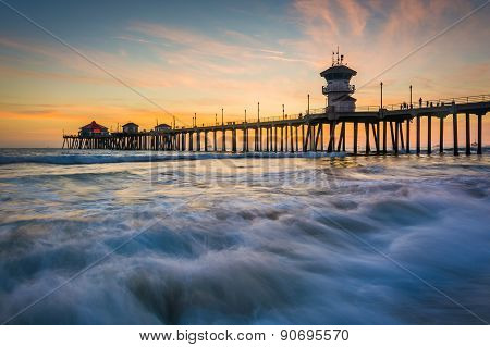 Waves In The Pacific Ocean And The Pier At Sunset, In Huntington Beach, California.