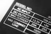 "Power rating. Power rating section of a power supply unit. Focus on ""Max Current"". Shallow depth of field. poster"