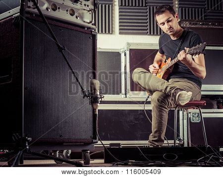 Man Recording Guitar Tracks In A Studio