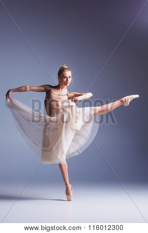 Young beautiful ballerina dancer dancing on a studio background