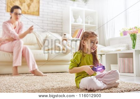 happy child girl playing video games. mother frustrating that her child playing video games