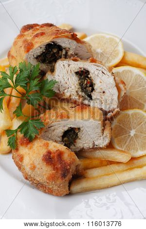 Chicken kiev served with french fries and lemon slices