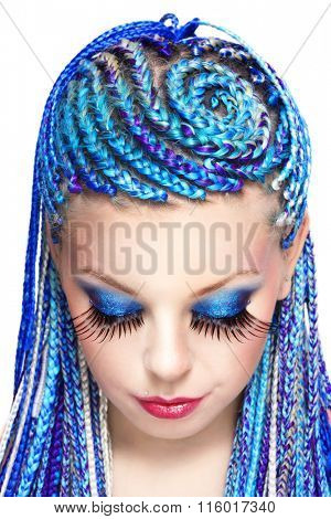 Girl with fancy blue braids hairdo and huge false eyelashes over white background