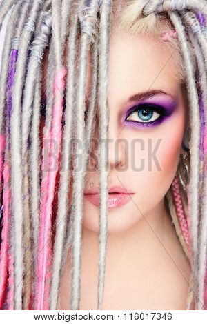 Portrait of young beautiful sexy girl with stylish bright make-up and dreadlocks