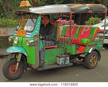 man is driving tuk-tuk in Bangkok, Thailand
