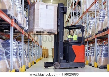 man with tablet pc operating forklift at warehouse