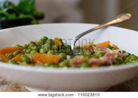Petit pois a la Francaise in bowl with spoon