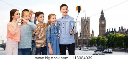 happy children with smartphone and selfie stick