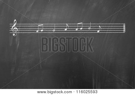 Music portative with G clef drawn with white chalk on blackboard