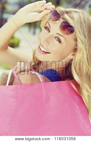 Instagram style photograph of beautiful, happy and fashionable young blond woman with heart shaped sunglasses and colorful shopping bags over her shoulder.
