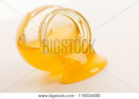 Sweet Sticky Golden Honey Flowing Out Of Lying Glass Jar.