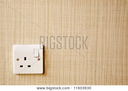 British Standard BS 1363 AC power socket at the corner of a wall poster