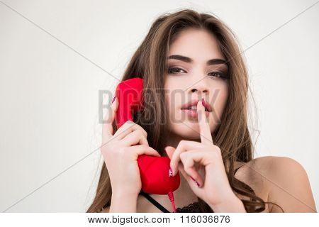 Portrait of a young pretty woman with red phone tube showing finger over lips isolated on a white background