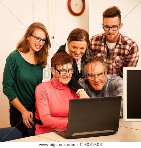 Group Of Adults Learning Computer Skills. Intergenerational Transfer Of Knowledge.