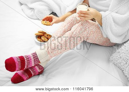 Woman in pajamas drinking milk with cookies on her bed