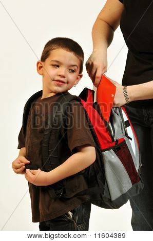 Mom getting packpack ready for son