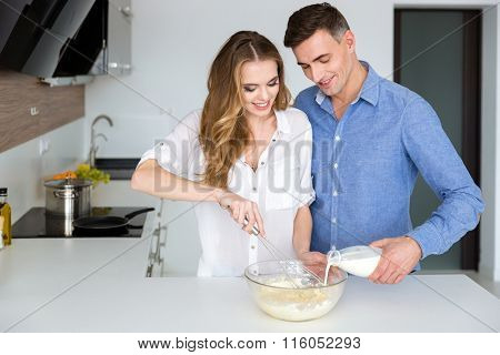 Beautiful couple mixing products in glass bowl with hand beater on the kitchen