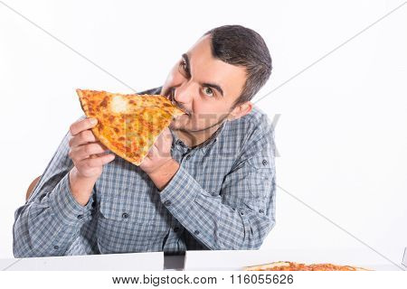 Young man biting a piece of vegetarian pizza
