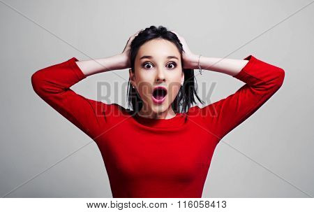 surprised and shocked teenage girl isolated against grey studio background