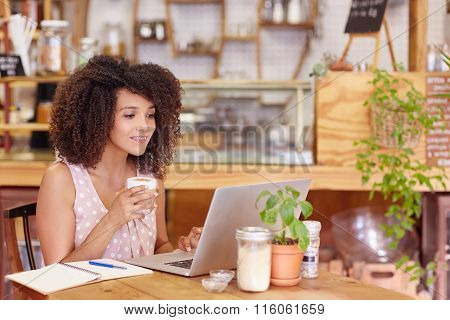 Female freelancer working in a coffee shop on her laptop