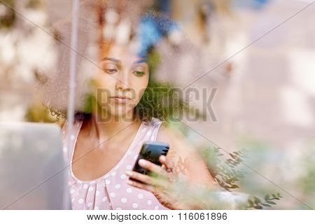 Woman using her phone seen through the window of cafe