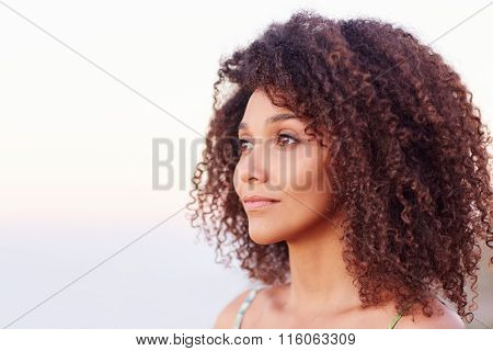 Mixed race woman with afro hair looking away serenely outdoors