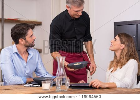 Senior waiter serving food to a young happy couple in a restaurant. Senior chef serving his specialty cuisine to young couple. Happy satisfied chef serving food to young woman.