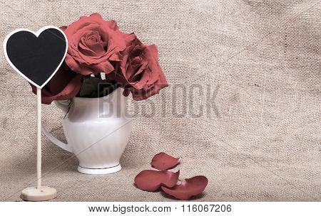 Pink Roses And Mini-board In The Form Of Heart In A White Jug Against A Sacking