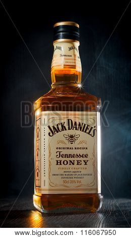 A bottle of whiskey, located on a wooden dark background, shrouded in white mist