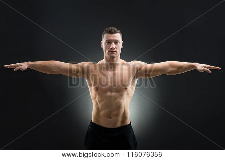 Confident Muscular Man Standing Arms Outstretched