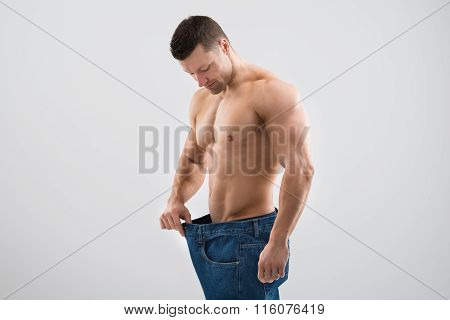Muscular Man Looking At Weight Loss While Holding Old Jeans