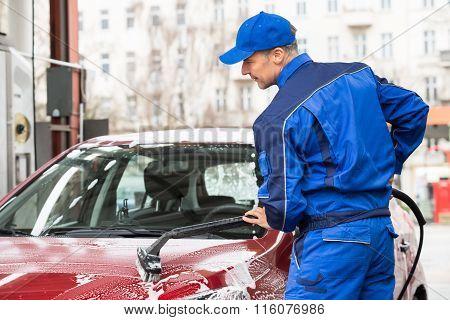 Manual Worker Washing Car At Service Station