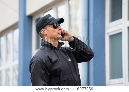 Security Guard Using Mobile Phone Outside Building